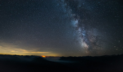A late summer wildfire burning deep in the Olympic National Park flares during this 30 second exposure taken from Hurricane Ridge Visitor Center