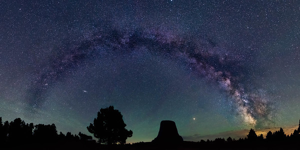The milky way arching over Devil's Tower with Mars and Andromeda visible. The greenish hue near the horizon is due to air glow.  This image is a 180deg x 90deg panorama, comprising of 9 images.