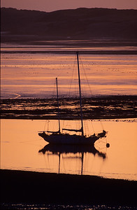 Sailboat in bay at low tide.  Taken at late sunset.  Morro Bay, California.