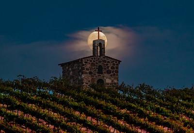 Moon rising behind vineyard chapel