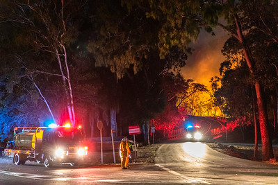 SES and firefighters watch the fire approach Pilbeam Drive
