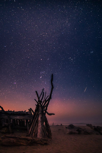 Rockaway Beach Oregon, a driftwood teepee stands under a blanket of stars in early Autumn.
