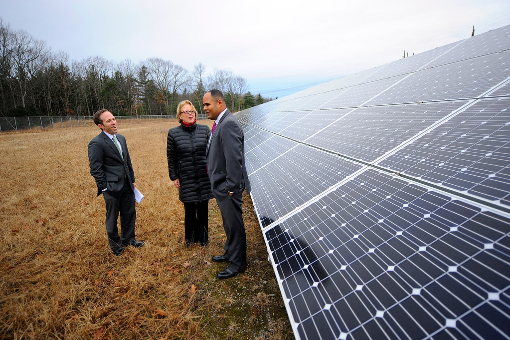 . Mass Department of Energy Resources Commissioner Mark Sylva, U.S. Rep. Niki Tsongas, and Lancaster Town Administrator Orlando Pacheco talk during the ribbon cutting ceremony for Lancaster\'s solar array on Route 70, Friday, December 7, 2013. SENTINEL & ENTERPRISE / BRETT CRAWFORD