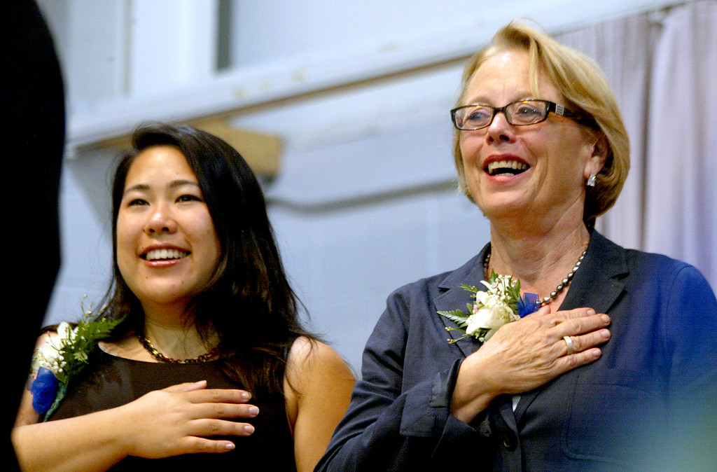 . Fitchburg Mayor Lisa Wong along with Rep. Niki Tsongas during the singing of the National Anthem by Amanda Breau at the Shriver Job Corps Graduation Ceremony at the Devens Campus in 2012. SUN/David H. Brow