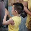 young boy at the temple offering a prayer