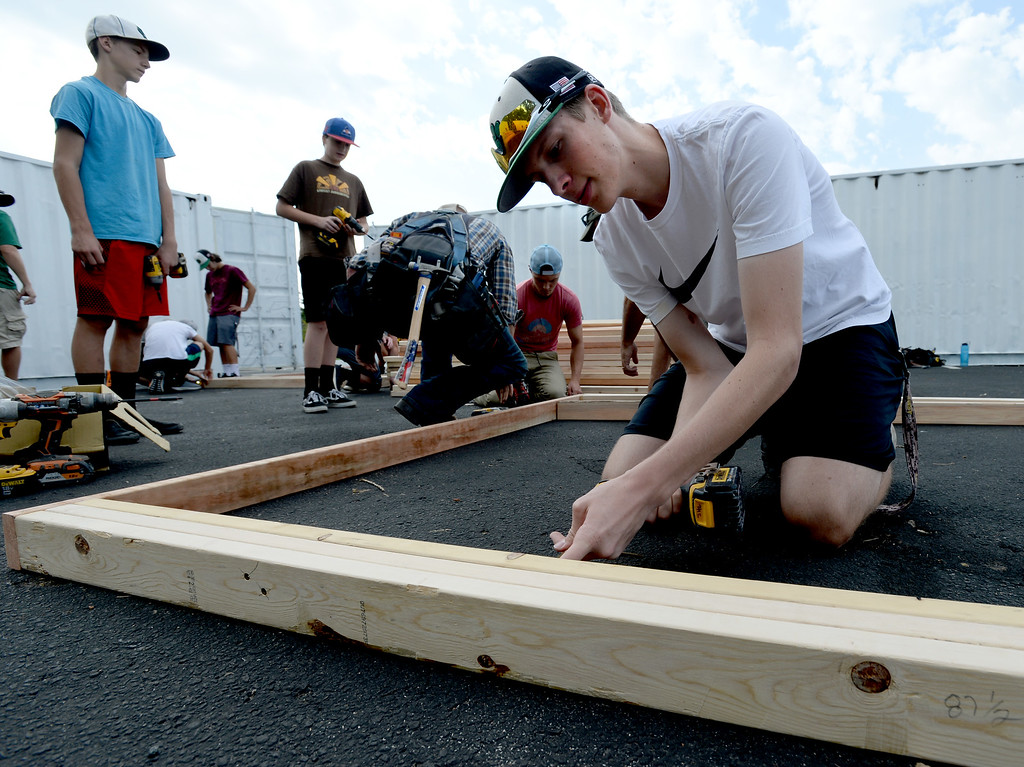 . NIWOT, CO - AUGUST 25:  Jaryd Meek, screws together boards for the container.  Niwot High School students help build classroom container buildings that will be used to address overcrowding at Niwot Elementary\'s partner school in Uganda through the Mwebaza Foundation for the last 10 years, Mwebaza Primary School. The Mwebaza Foundation, which started at Niwot Elementary, is working with the nonprofit, Homes of Living Hope, to coordinate this project. Homes of Living Hope sends shipping containers all over the world for use as schools, clinics, etc. on August 25, 2018.  (Photo by Cliff Grassmick/Staff Photographer)