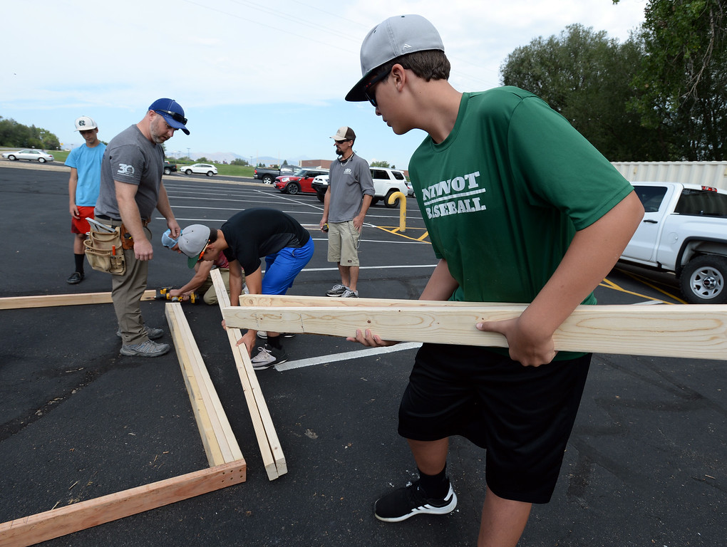 . NIWOT, CO - AUGUST 25:  Gage Gruidel brins in 2 by 4\'s to the crew.  Niwot High School students help build classroom container buildings that will be used to address overcrowding at Niwot Elementary\'s partner school in Uganda through the Mwebaza Foundation for the last 10 years, Mwebaza Primary School. The Mwebaza Foundation, which started at Niwot Elementary, is working with the nonprofit, Homes of Living Hope, to coordinate this project. Homes of Living Hope sends shipping containers all over the world for use as schools, clinics, etc. on August 25, 2018.  (Photo by Cliff Grassmick/Staff Photographer)