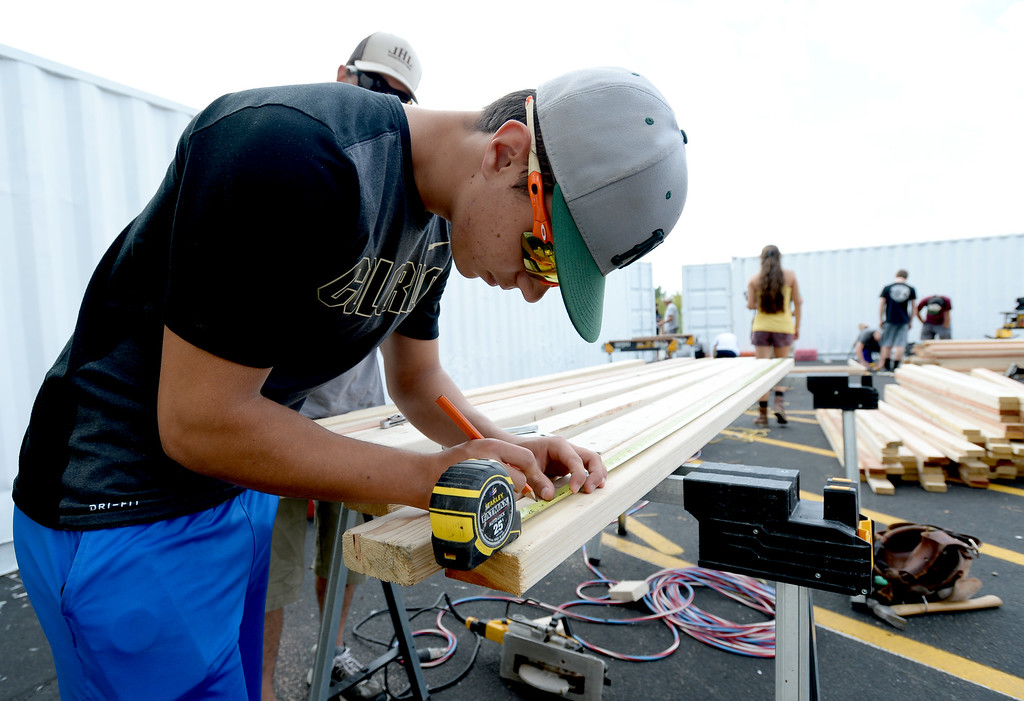 . NIWOT, CO - AUGUST 25:  Josh Strid measures a board during the construction. Niwot High School students help build classroom container buildings that will be used to address overcrowding at Niwot Elementary\'s partner school in Uganda through the Mwebaza Foundation for the last 10 years, Mwebaza Primary School. The Mwebaza Foundation, which started at Niwot Elementary, is working with the nonprofit, Homes of Living Hope, to coordinate this project. Homes of Living Hope sends shipping containers all over the world for use as schools, clinics, etc. on August 25, 2018.  (Photo by Cliff Grassmick/Staff Photographer)