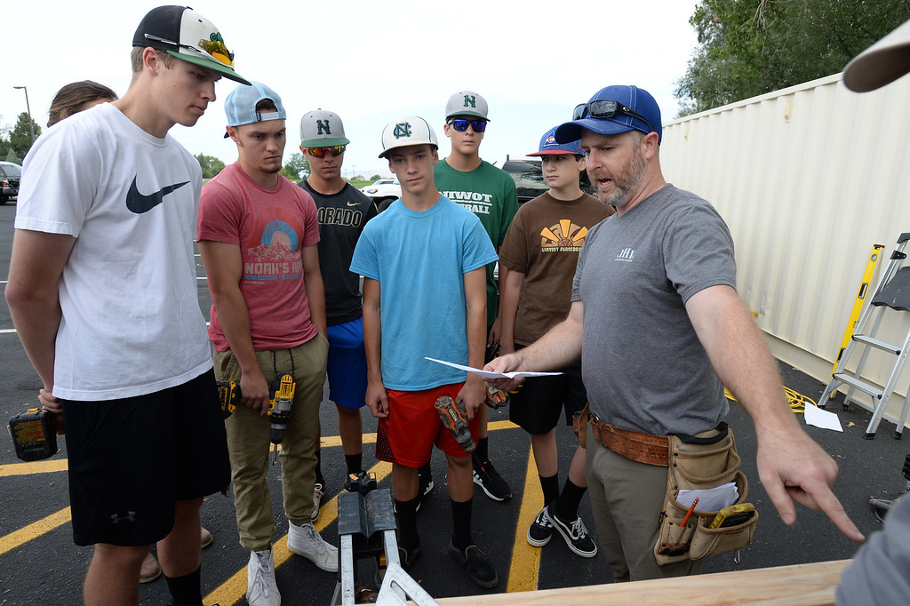 . NIWOT, CO - AUGUST 25:  Joel Reeves, right, explains the building plans to the Niwot students. Niwot High School students help build classroom container buildings that will be used to address overcrowding at Niwot Elementary\'s partner school in Uganda through the Mwebaza Foundation for the last 10 years, Mwebaza Primary School. The Mwebaza Foundation, which started at Niwot Elementary, is working with the nonprofit, Homes of Living Hope, to coordinate this project. Homes of Living Hope sends shipping containers all over the world for use as schools, clinics, etc. on August 25, 2018.  (Photo by Cliff Grassmick/Staff Photographer)