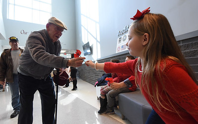 Seven-year-old Abigail Imboden, extends her hand to give Navy Veteran Warren Bray, of Palmer Township, a poppy as he arrives at the ceremony. Phillipsburg area veterans Sunday, Nov. 11, 2018  were honored during the 21st annual William L. Nixon tribute. Hundreds attended the event at Phillipsburg High School in Lopatcong Township, in which the U.S. Department of Veterans Affairs has honored as a regional site for the observance of the commemoration.