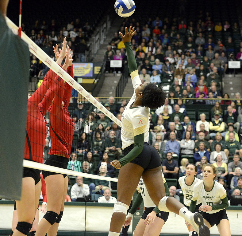 Breana Runnels of Colorado State tips against the UNLV block during Saturday's match at Moby Arena.