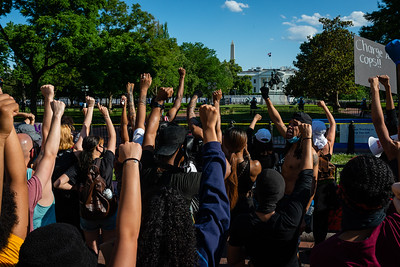 Demonstrators raise their fists outside of the White House in Washington, DC on May 30, 2020.