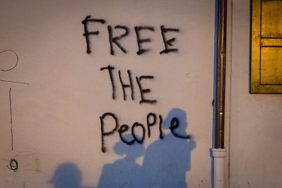"""People's shadows are seen on the wall where writing reads, """"Free the People"""" in Washington, DC on May 31, 2020."""