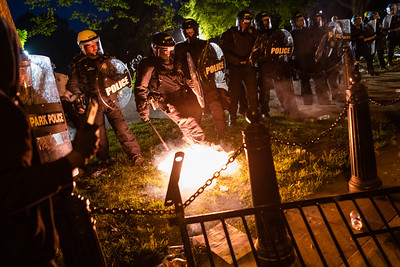 A police officer tries to put out a firecracker before kicking it back into the crowd outside of the White House in Washington, DC on May 30, 2020.