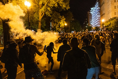 Protesters attempt to put out a tear gas canister before it spread outside of the White House in Washington, DC on May 30, 2020.