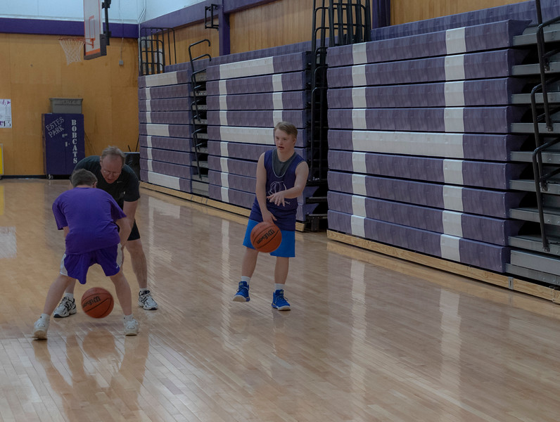 Mark Query, left and his dad practice dribbling while Mark's best friend Noah Olson looks on. Both boys have down syndrome, with Mark living with autism. T
