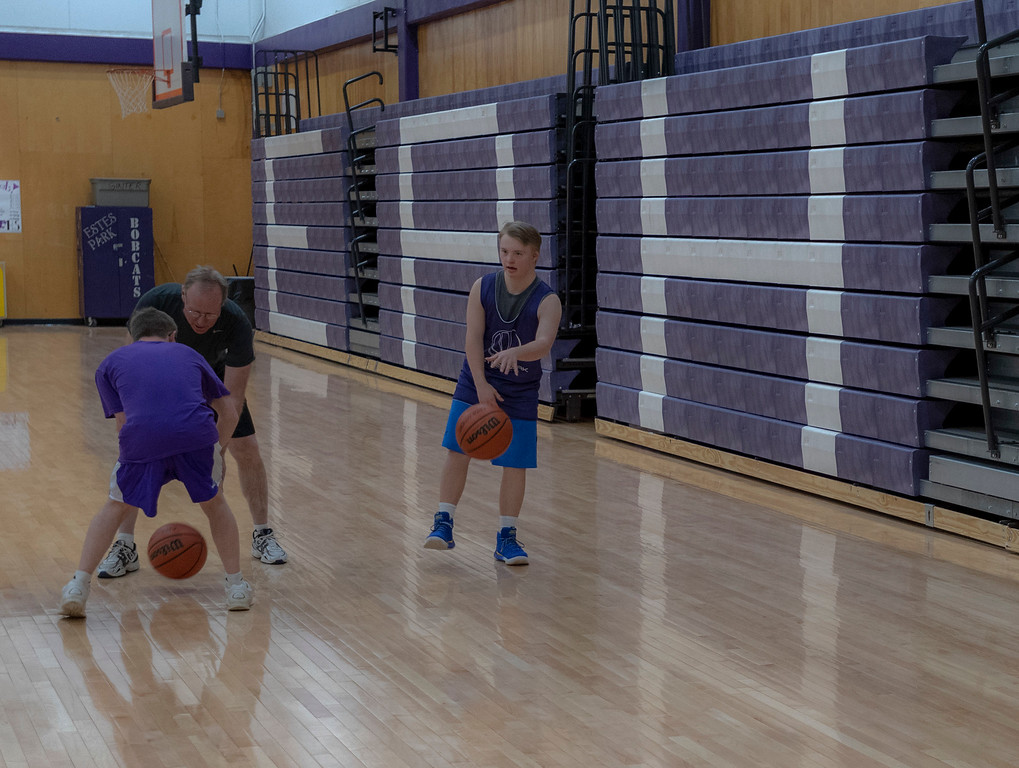 . Mark Query, left and his dad practice dribbling while Mark�s best friend Noah Olson looks on. Both boys have down syndrome, with Mark living with autism. T