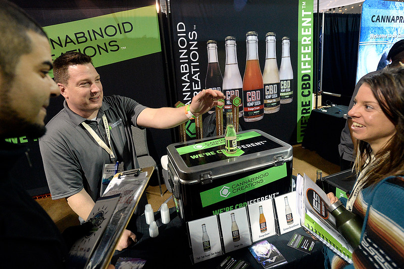 Keith Karp with Cannabinoid Creations, center, tells Kat Brickner of Longmont, right, and Kareem Kandil of Lombardo, Illinois, left, about the different flavors of CBD Hemp Soda the company sells Friday, April 7, 2018, during the Noco Hemp Expo at the Ranch in Loveland. (Photo by Jenny Sparks/Loveland Reporter-Herald)