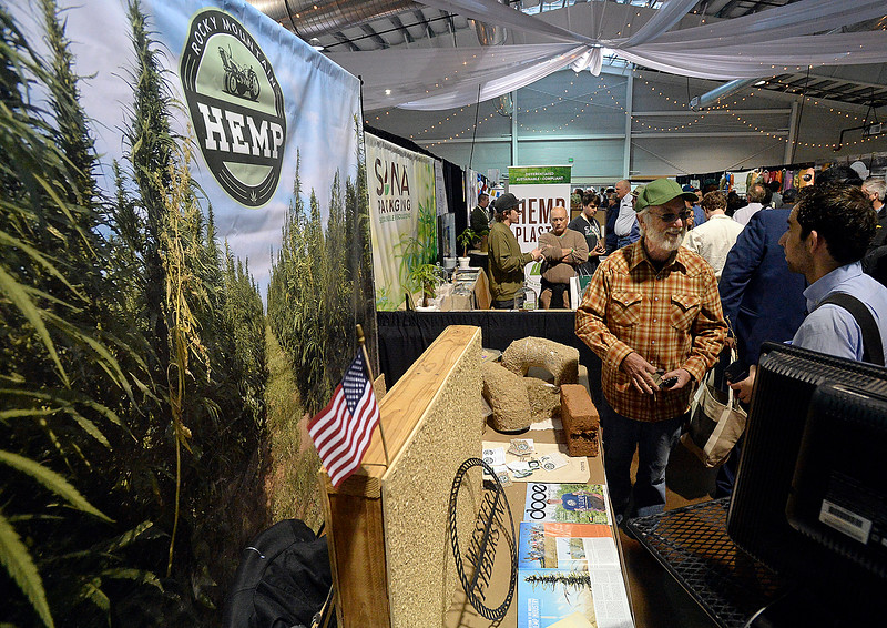 Mike McGuire, right, talks to Michael Scherr, far right, about the building materials made with hemp at the Rocky Mountain Hemp/Western Fibers booth Friday, April 7, 2018, during the Noco Hemp Expo at the Ranch in Loveland. (Photo by Jenny Sparks/Loveland Reporter-Herald)