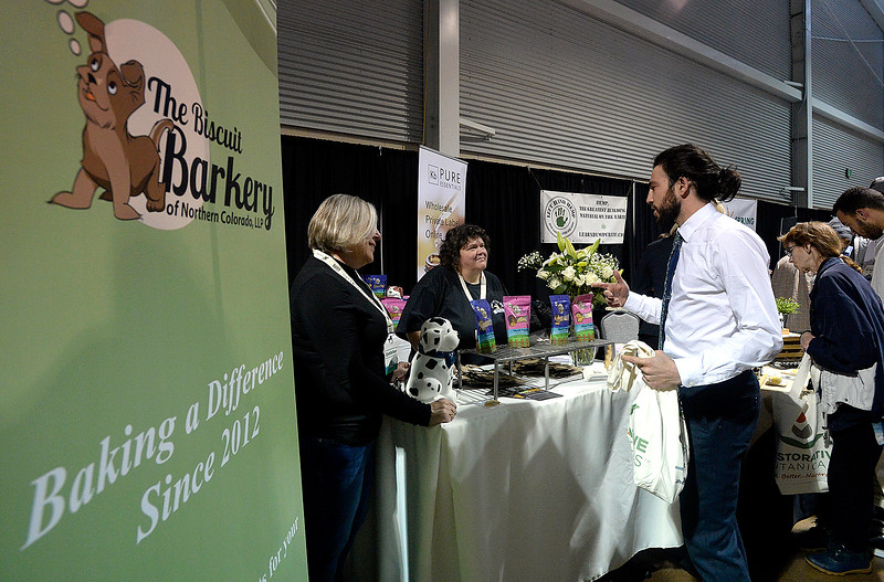 Nan Barron, left, and Val Downing, center, co-owners of The Biscuit Barkery, chat with Steven Turetsky, right, about their products Friday, April 7, 2018, during the Noco Hemp Expo at the Ranch in Loveland. The Loveland based company makes dog treats with CBD in them.  (Photo by Jenny Sparks/Loveland Reporter-Herald)