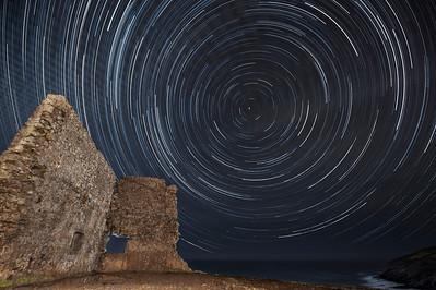 """STARTRAILS, desde Santa Justa (Cantabria). Esta fotografía es el resultado de unir, a través de un programa informático STARTRAILS, 292 fotografías de 25 segundos de exposición cada una. Un total de 122 minutos.  F/2.8 Focal 14 mm.  ISO 1250  Las """"rayitas"""" son rastro de las estrellas. Para conseguir dicho rastro, se ha colocado la cámara en un trípode. A través de un intervalómetro conectado a la cámara lo hemos programado para que haga indefinidas fotografías de la misma exposición (En este caso fue necesario una exposición de 25 segundos). Como  bien sabemos, La Tierra da una vuelta cada 24 horas sobre su mismo eje. El eje de rotación de la Tierra parece siempre apuntar en la misma dirección, que coincide muy aproximadamente con la posición de la estrella polar hace el norte. Así que después de estar dos horas y media bajo las estrellas una noche de invierno hasta que las nubes aparecieron, hemos podido unir con STARTRAILS las 292 fotografías que vimos más limpias de nubes, para obtener este resultado. La iluminación del """"castillo"""" es nada más y nada menos que la luz que hacían los coches que se acercaban a la playa de Tagle. La función del programa STARTRAILS es unir una foto encima de otra, pero sólo añadiendo la luz de cada fotografía. De ahí los rastros de las estrellas y la iluminación de las ruinas. También en una de las ventanas se puede apreciar algo de luz a su alrededor, ya que en una de las tomas fui a disparar una vez con el flash, para hacer que en la fotografía final tuviera esa ventana algo más de protagonismo y relieve.  También podemos ver unas trazas difuminadas en el cielo transversales a los rastros de las estrellas que son las nubes que dejan los aviones en su paso, como podemos apreciar mucho mejor  en el siguiente Time-Lapse realizado con las mismas fotografías."""