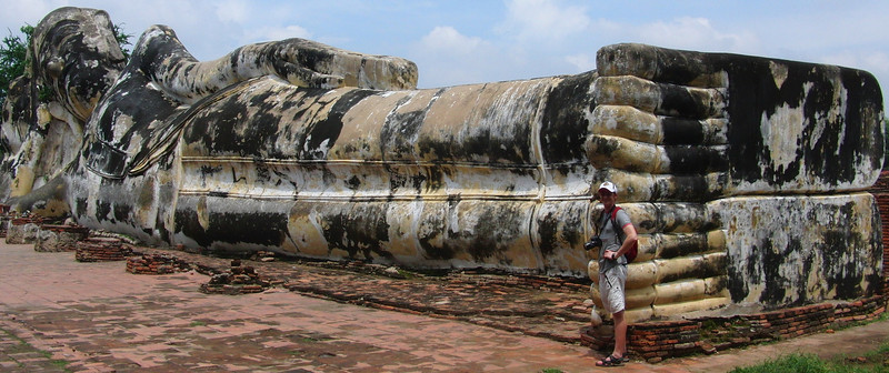 Today's daily travel photo is of Nomadic Samuel Jeffery exploring the Ancient Thai ruins of a Reclining Buddha in Ayutthaya, Thailand.