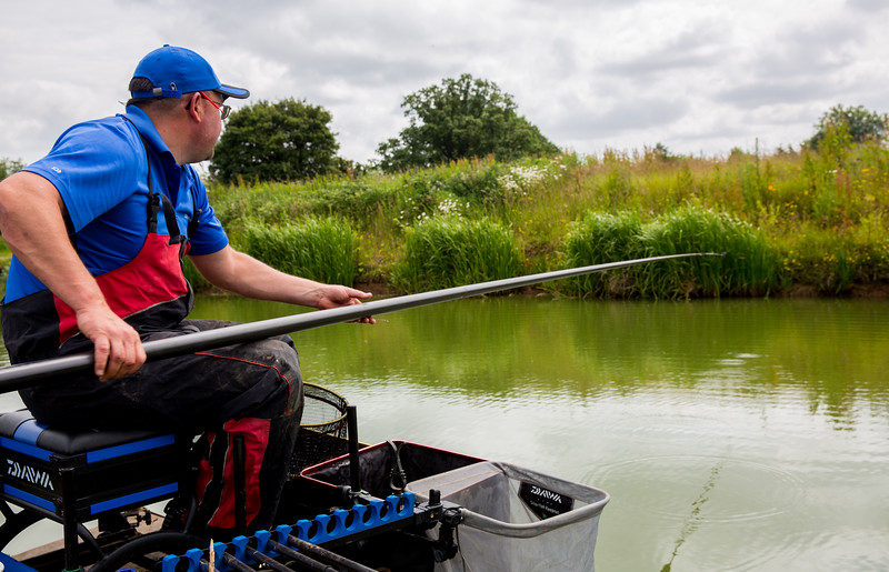 Shipping a baited pole rig across to the far bank swim.