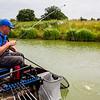 Will Raison preparing to net an F1 carp splashing on the surface.