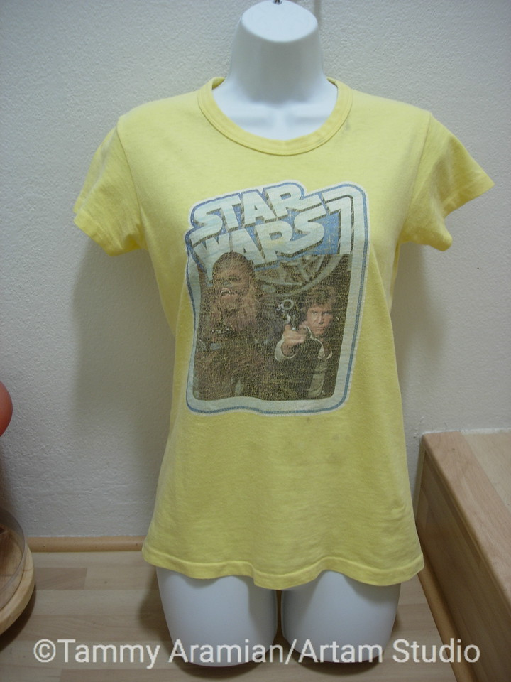 1977-78 yellow women's cut t-shirt (I'll have to check for size and fiber) with pre-ironed-on transfer Star Wars graphic of Chewbacca and Han Solo. Through washing the transfer has developed that beautiful vintage crackle look that is now done on purpose and highly prized. The t-shirt is in very good condition for its age with no stains or holes, and since retiring from active wardrobe (guessing 1979-81) was washed and has been protectively stored. Why buy retro when you can buy authentic! <br /> $75