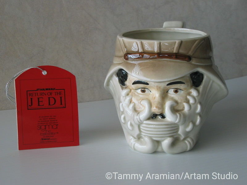 Sigma 1983 ceramic hand-painted mug of Lando Calrissian in Jabba's guard disguise with original hang tag. Return of the Jedi branded. Never displayed or used for beverages, no chips or crazing. <br /> $300
