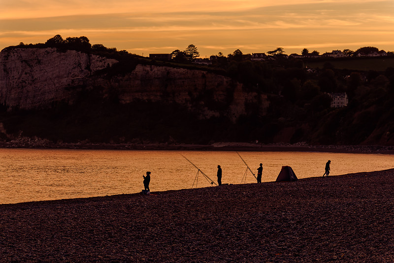 Fishermen on the beach, hoping to benefit from the incoming tide, <br /> as the sun sets over Beer Head. 29th September 2018.