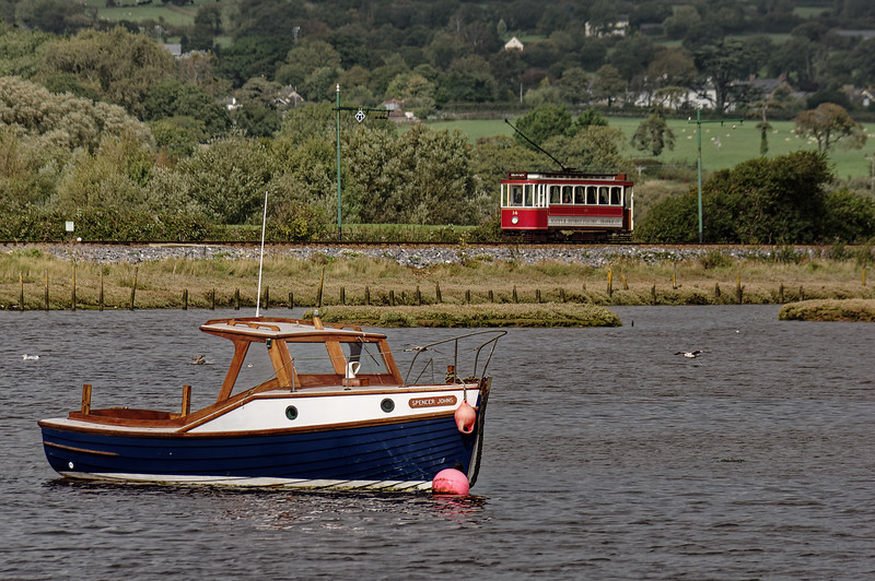 """""""Spencer Johns"""" moored on the River Axe Estuary, while Tram No. 14 passes in the background. 6th October 2015."""