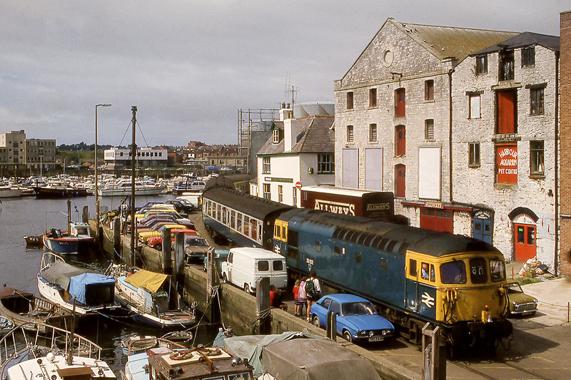 22nd Aug 82  33102 eases the Boat Train  round the 1938 curve on the Weymouth Harbour  Tramwa., Taken from the Town Bridge.   Note the warning bell on the front