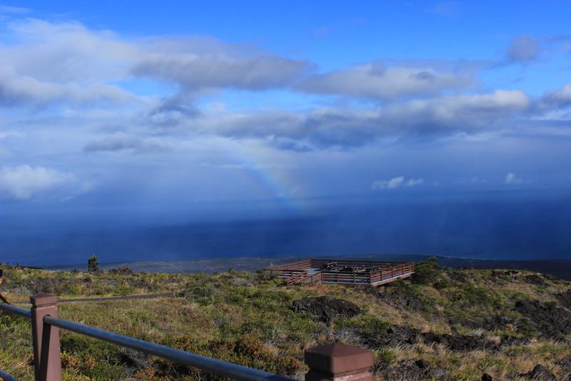 Rainbow over ocean at overlook in hawaii