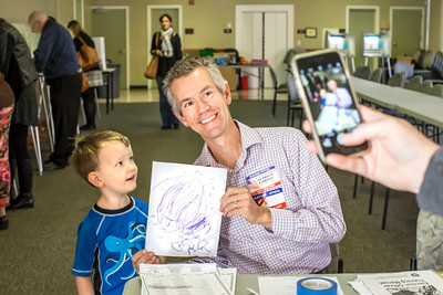 """Krystin Leonhardt snaps a photo of her son, Logan, turning in his """"ballot"""" to poll worker Eric Johnson, who also serves as president of the Sierra Curtis Neighborhood Association."""