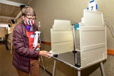 Elections worker Sandra Christensen cleaned each polling station after every use at the Sierra 2 Center in Curtis Park on Election Day 2020.