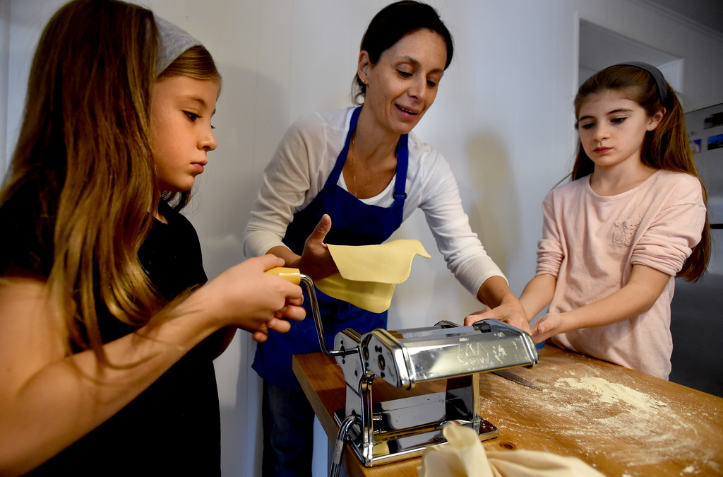 . Luce Steen, left, Claudia Steen, and other daughter, Sophia, flatten the pasta dough. Claudia Steen, her husband, Ted, father-in-law, Jim, and daughters, Sophia and Luce, were  making fresh Italian pasta and Norwegian lufsa (a soft potato bread) as part of their nontraditional Thanksgiving meal.  Cliff Grassmick  Photographer November 22, 2017