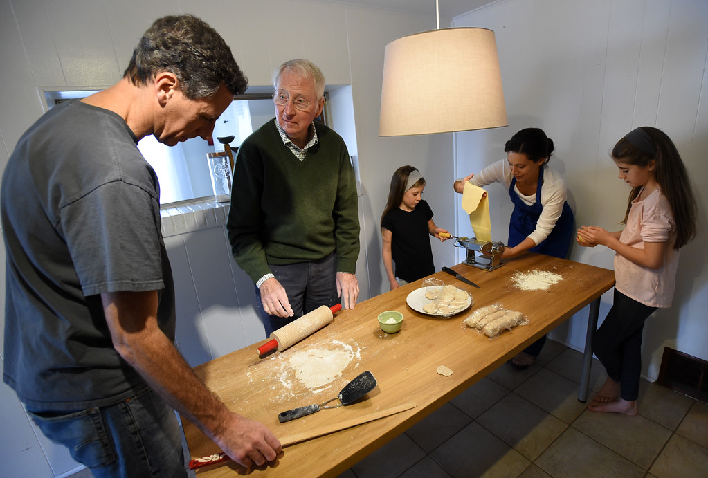 . Ted Steen, his father, Jim, makes lufsa, while Luce Steen, left, Claudia Steen, and other daughter, Sophia, flatten the pasta dough. Claudia Steen, her husband, Ted, father-in-law, Jim, and daughters, Sophia and Luce, were  making fresh Italian pasta and Norwegian lufsa (a soft potato bread) as part of their nontraditional Thanksgiving meal.  Cliff Grassmick  Photographer November 22, 2017