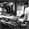 Archie Soloman and Luther Minor at work on plate finishing machine in the Transcript Pressroom.