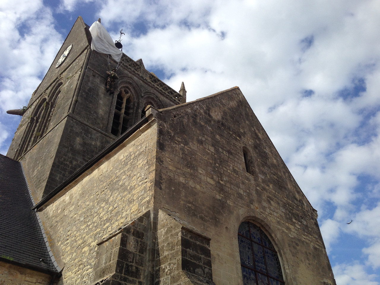 St. Mere Eglise, famous for this scene. On June 6, 1944, a parachutist named John Steele hung for several hours when his chute was caught on part of the church roof. Every year the citizens of the town recreate this event to honor his and his comrades' sacrifices.