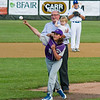 Brooke Bishop throws out the ceremonial first pitch, with Dick Alcombright and granddaughter Mila looking on.
