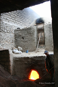 Large kiln for firing the ceramic tiles and vases. Kiln is fired by burning  crushed olive pits, which creates large clouds of black smoke.
