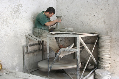 Potter at the wheel creating a large vessal at the ceramics factory. Note that the potter's wheel is driven by foot power.
