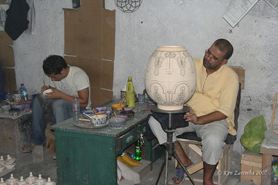 Men drawing the intricate designs on  the ceramic pieces