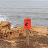 Danger warning sign on rugged sandstone cliffs on California's Pacific coast