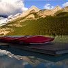 The red canoes stacked on the boathouse dock add a sense of vibrancy to the scenery.