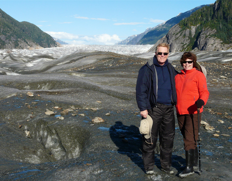 A boomer man and woman pose in Alaska expedition clothes in front of a glacier.