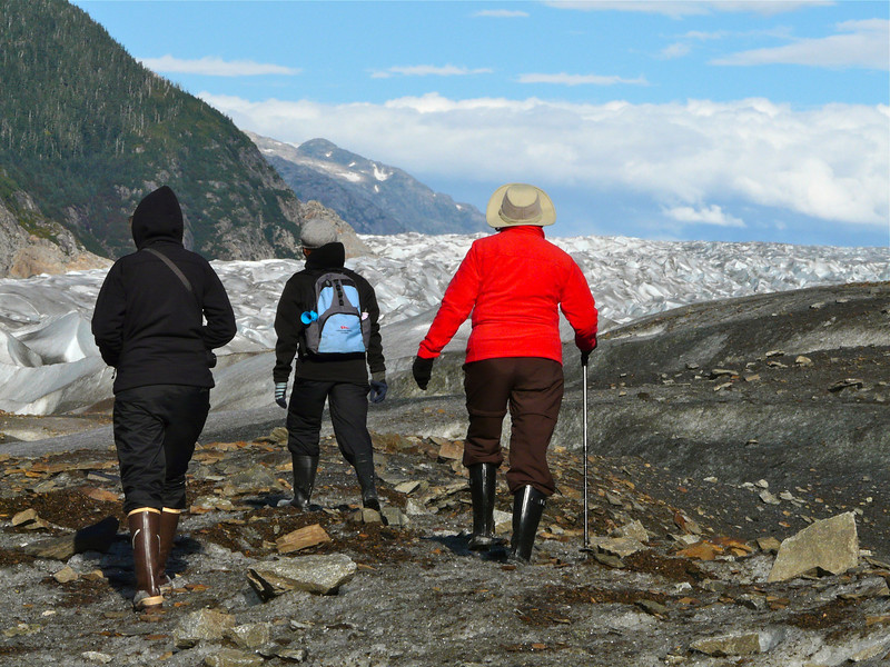 Three people walking towards a glacier