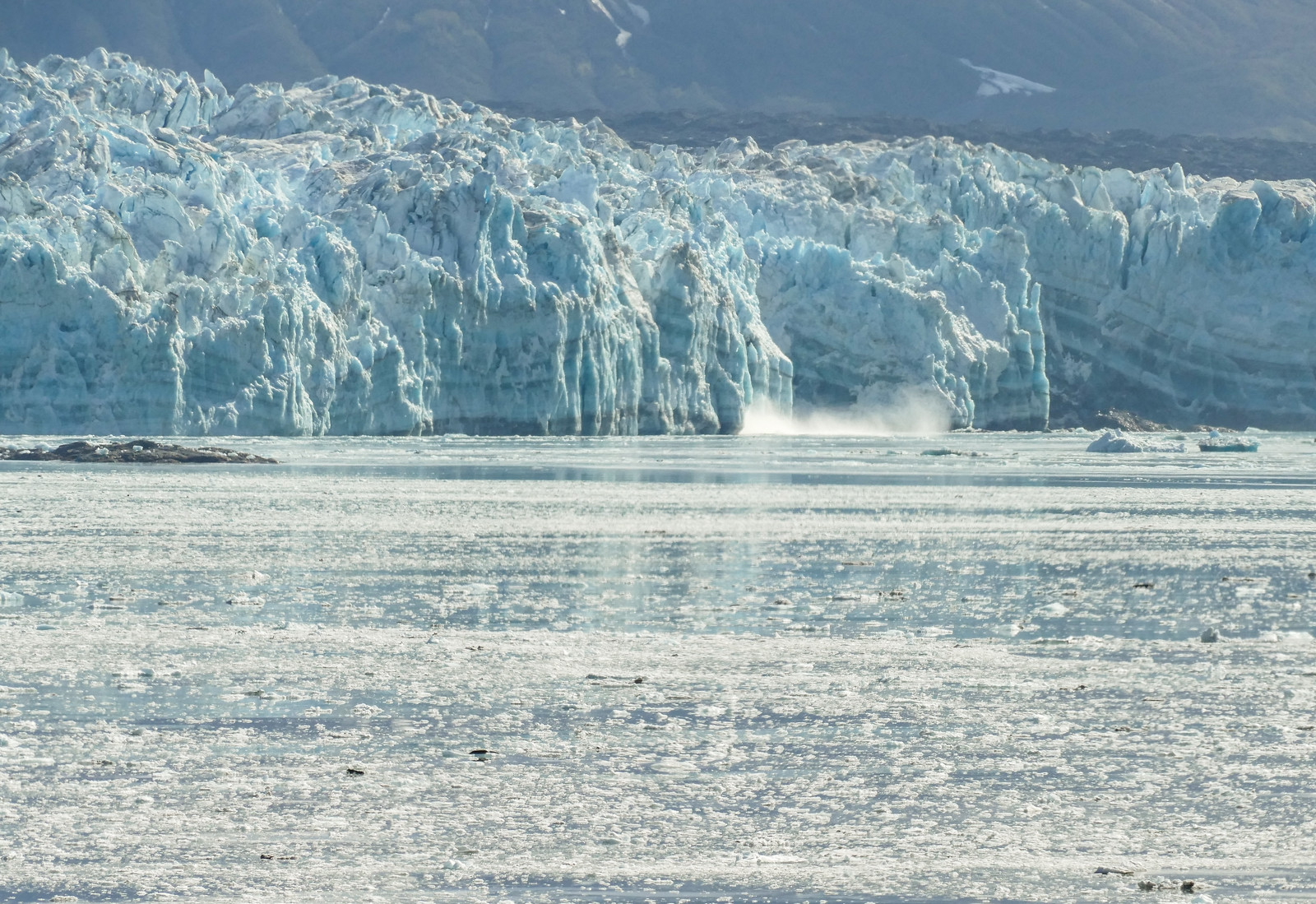 Mist rises from the front of a glacier after a calving.