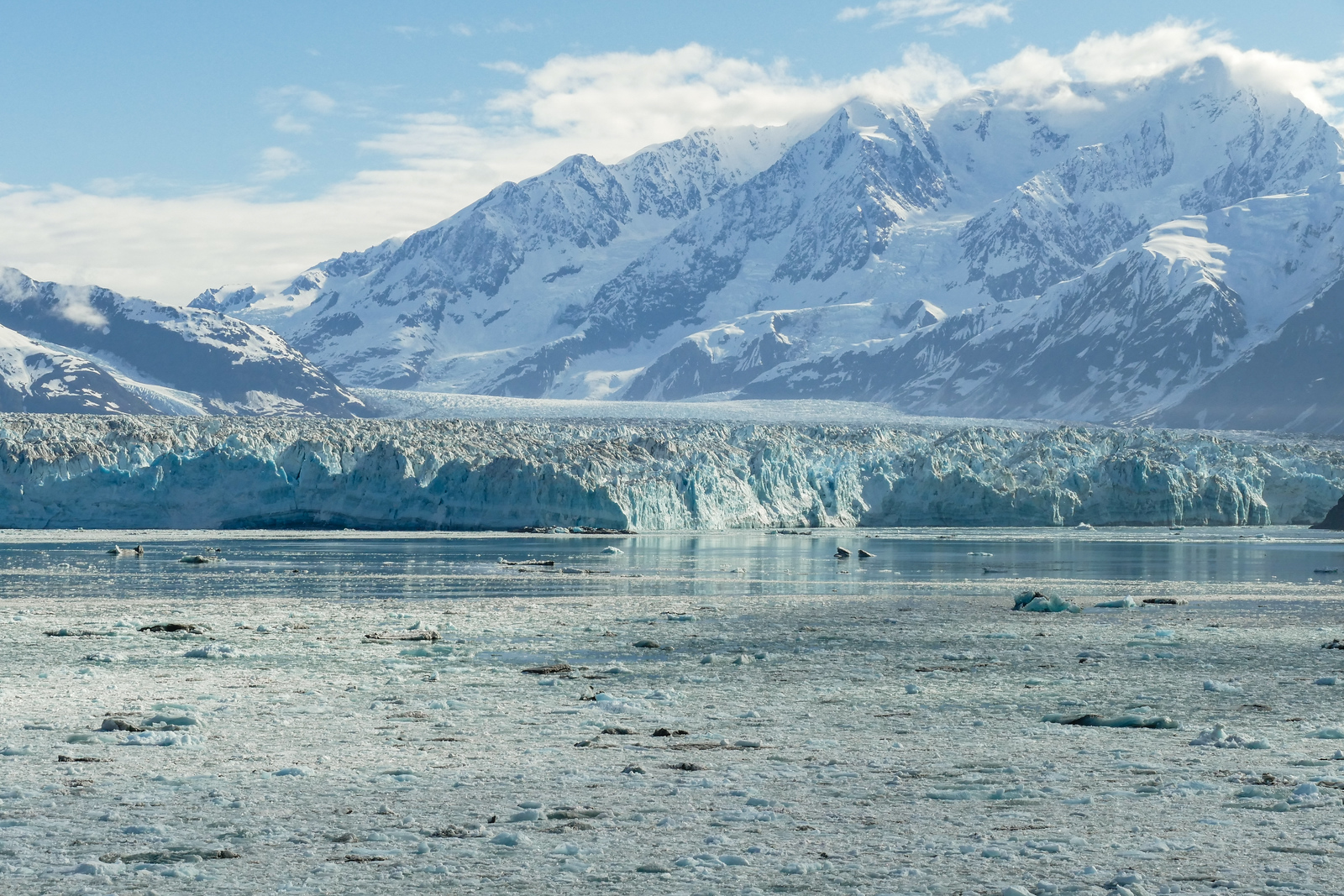 Snow capped mountains rise behind the ice face of Hubbard Glacier.